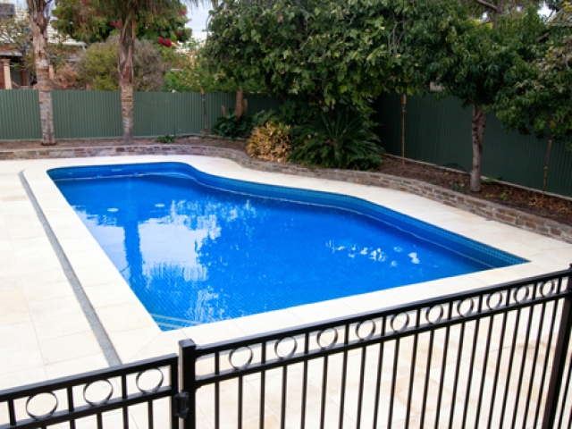 sandstone paved pool with safety barrier fence