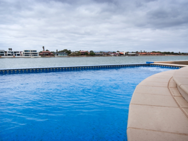 low angle pool with tiled exterior overlooking west lakes