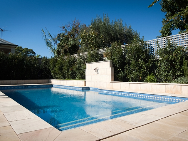 elegant custom pool design with stone pavers with upright fountain