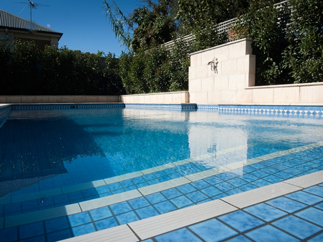 custom pool design with water feature with landscape surrounding