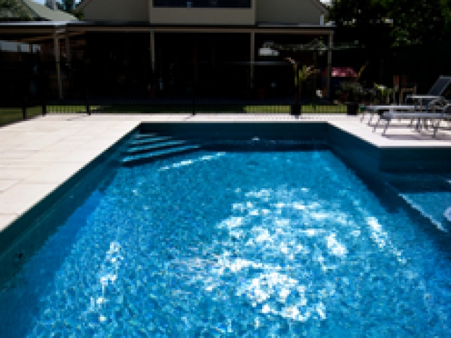 outdoor in ground pool with sunny sky