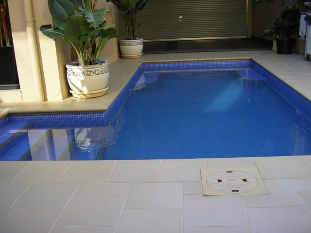in ground pool with shady overhead lighting