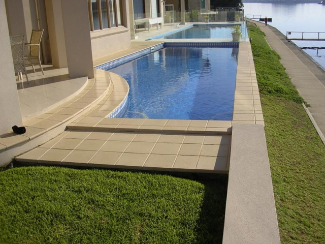 outdoor concrete pool with waterfront view
