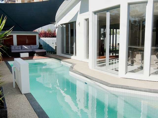 modern customised pool with stone border and upright water features