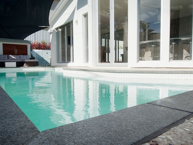 modern customised pool with stone border bespoke upright water feature