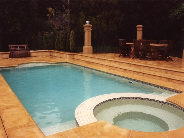 roman grecian style concrete in ground pool featuring spa